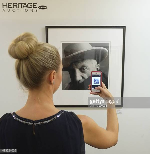 A visitors snaps a picture of an Irving Penn portrait of Pablo Picasso exhibited by Heritage Auctions during the LA Mart in Los Angeles California on...