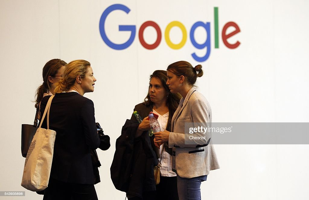 Visitors speak in front of a Google logo during the Viva Technology show on June 30, 2016 in Paris, France. Viva Technology Startup Connect, the new international event brings together 5,000 startups with top investors, companies to grow businesses and all players in the digital transformation who shape the future of the internet.