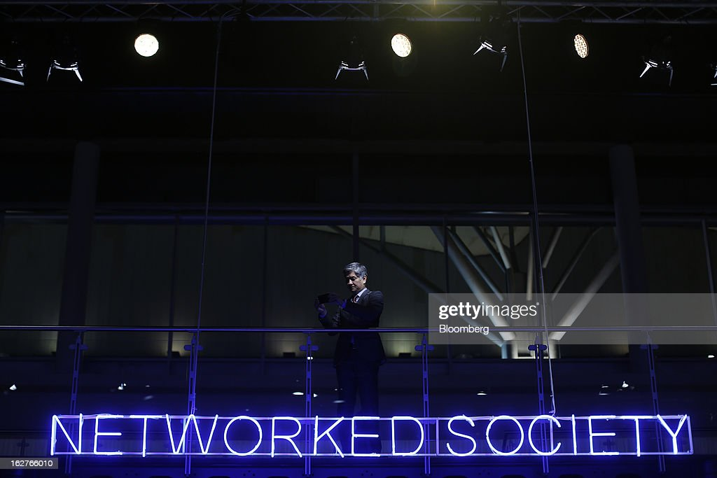 Visitors stand above a neon sign reading 'Networked Society' inside the Ericsson AB pavilion at the Mobile World Congress in Barcelona, Spain, on Tuesday, Feb. 26, 2013. The Mobile World Congress, where 1,500 exhibitors converge to discuss the future of wireless communication, is a global showcase for the mobile technology industry and runs from Feb. 25 through Feb. 28. Photographer: Simon Dawson/Bloomberg via Getty Images