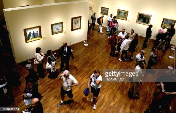 Visitors stand among paintings by Dutch post impressionist painter Vincent van Gogh at Vittoriano museum in central Rome on October 9 2010The central...