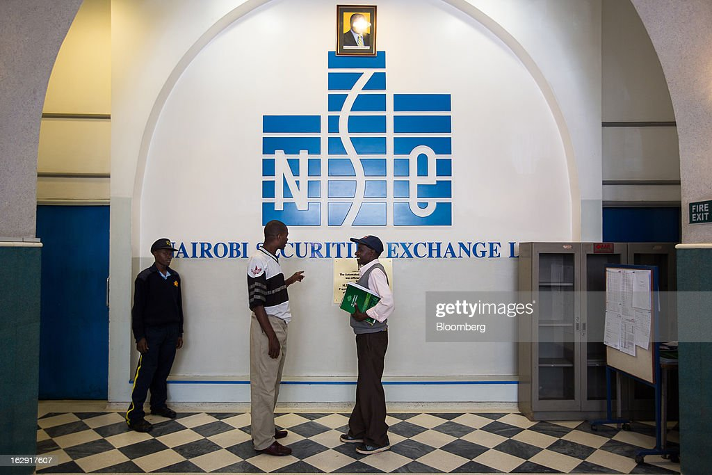 Visitors stand and talk in front of a logo inside the Nairobi Stock Exchange (NSE) in Nairobi, Kenya, on Friday, March 1, 2013. Next week's presidential vote will be the first since disputed elections in 2007 triggered ethnic fighting in which more than 1,100 people died and another 350,000 fled their homes. Photographer: Trevor Snapp/Bloomberg via Getty Images