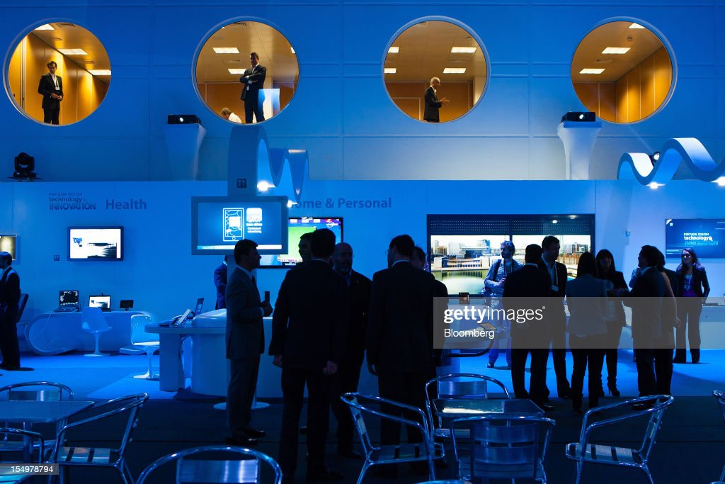 Visitors stand and talk in the Portugal Telecom SGPS showroom at the Technology and Innovation conference in Lisbon, Portugal, on Monday, Oct. 29, 2012. 'We believe prices in our domestic market are already low enough,' Portugal Telecom SGPS chief excecutive officer Zeinal Bava said. Photographer: Mario Proenca/Bloomberg via Getty Images
