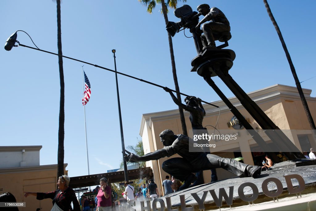 Visitors stand around a statue at the Universal Studios Hollywood theme park in Hollywood, California, U.S., on Thursday, Aug. 15, 2013. NBC Universal, majority owned by Comcast Corp., operates some of the most-watched U.S. cable TV channels, in addition to its flagship broadcast network, a film studio and the Universal Studios amusement parks. Photographer: Patrick T. Fallon/Bloomberg via Getty Images