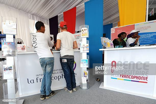 Visitors stand at a booth as they visit the 'Village de la Francophonie' on November 25 2014 in Dakar ahead of the 15eme Sommet de la Francophonie...