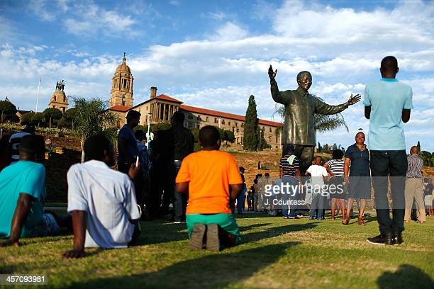 Visitors stand at the base of the statue of Former South African President Nelson Mandela that was unveiled at the Union Buildings on December 16...