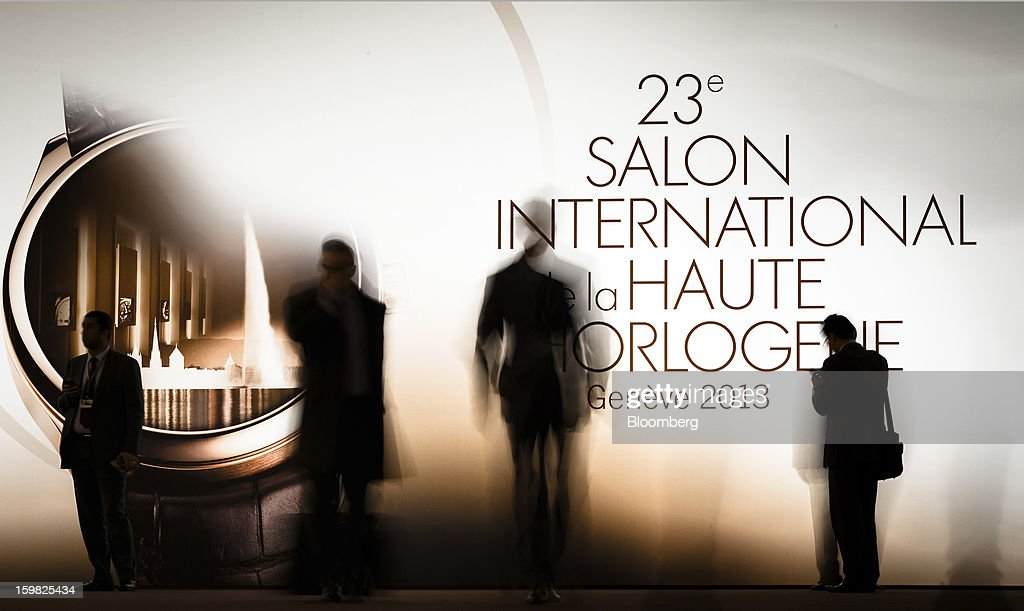Visitors stand before an illuminated advertisement as they arrive for the first day of the Salon International de la Haute Horlogerie (SIHH) watch fair in Geneva, Switzerland, on Monday, Jan. 21, 2013. The Swiss watch industry slowed in the second half of 2012 as sales of timepieces and jewelry in Hong Kong, the biggest market for Swiss watchmakers, declined in August and October. Photographer: Valentin Flauraud/Bloomberg via Getty Images