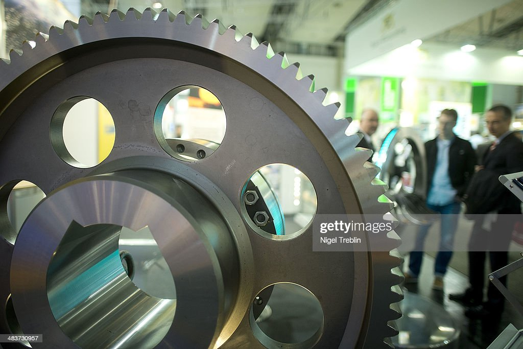 Visitors stand behind a gear wheel at the Kownatzki stand at the Hannover Messe industrial trade fair on April 10, 2014 in Hanover, Germany. The Netherlands is the official partner Country of this year's fair with more than 5000 companies showcasing their latest industrial products and solutions. The Hannover Fair will run from April 07-11.