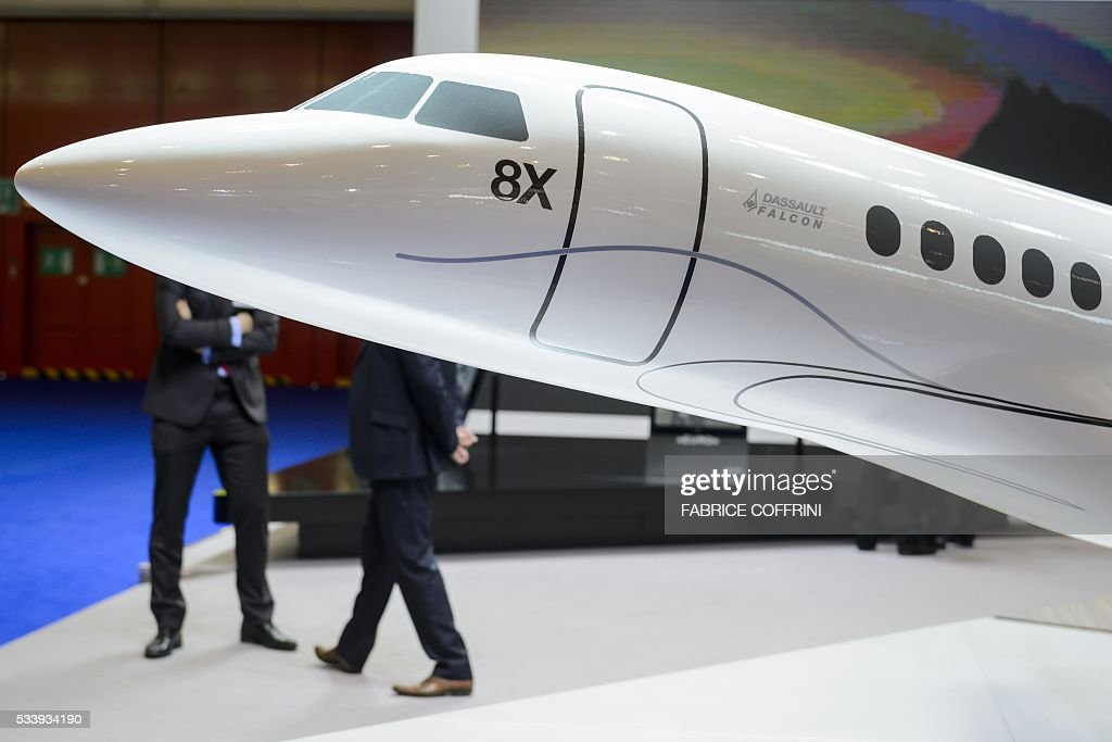 Visitors stand behind a scale model of Falcon 8X of the french company plane maker Dassault Aviation during the European Business Aviation Convention & Exhibition (EBACE) on May 24, 2016 in Geneva. COFFRINI