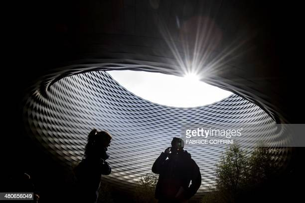 Visitors stand beneath the roof of the exhibition hall designed by Basel's architects Herzog de Meuron during the media day of 42nd edition of...