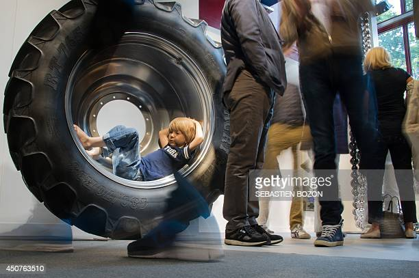 Visitors stand by a work of art by Danish artist Michael Elmgreen and Norvegian artist Ingar Dragset called 'Papa Was A Rodeo' on June 17 2014 during...