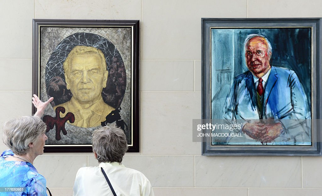 Visitors stand in front of a gallery with portraits of former German Chancellors Gerhard Schroeder (L) and Helmut Kohl at the Chancellery in Berlin during an open day of the German government on August 25, 2013. The German Chancellery as well as federal ministries traditionally open their doors for the public once a year.