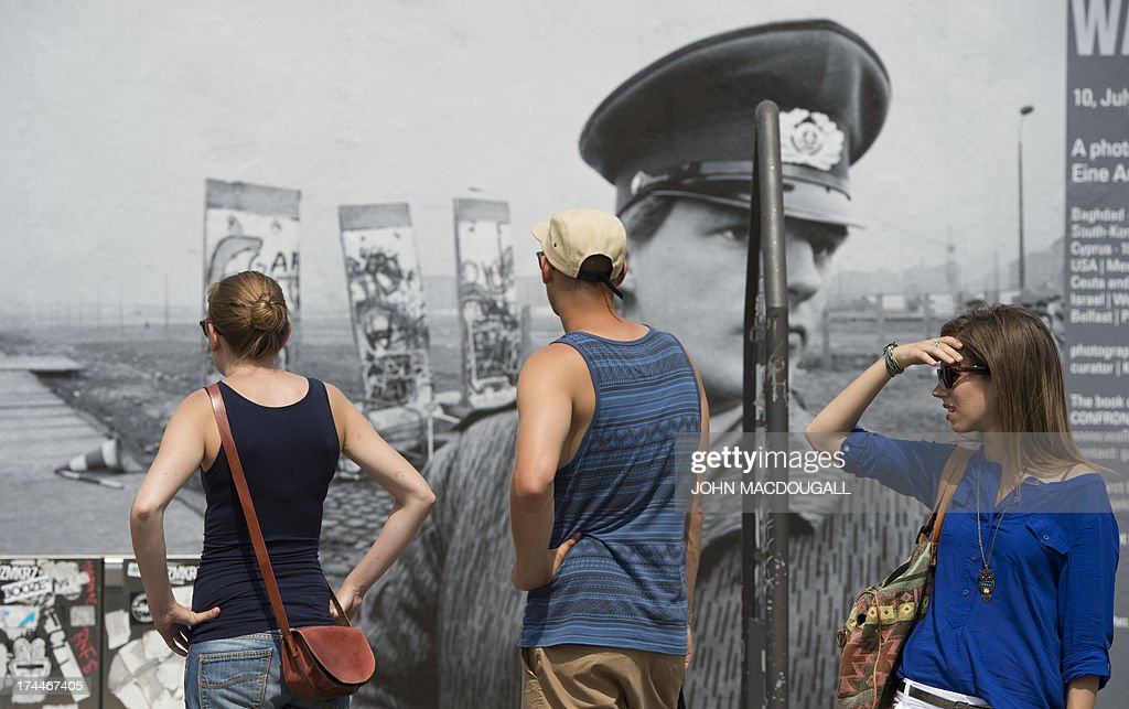 Visitors stand in front of a giant photograph showing sections of the Berlin wall in 1989 at the 'Wall on Wall' exhibition by German photographer Kai Wiedenhoefer displayed on a remaining section of the Berlin wall July 26, 2013. Wiedenhoefer's 'Wall on Wall' project features giant panoramic photographs of walls taken in Northern Ireland, Iraq, Cyprus, the West Bank, Morocco, South Korea and the border between the United States and Mexico. The exhibition takes place between10 July and 13 September 2013.
