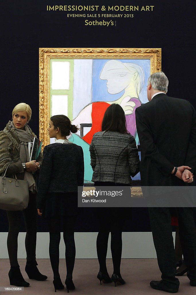 Visitors stand in front of a painting by Pablo Picasso entitled 'Femme assise pres d' une fenetre,' 1932, on January 31, 2013 in London, England. The piece makes up a selection of works by artists including Monet, Miro, Picasso and Richter and is estimated to sell for between 25-35 Million GBP at auction in the 'Impressionist and Modern Art' evening sale at Sotheby's auction house on February 5, 2013.