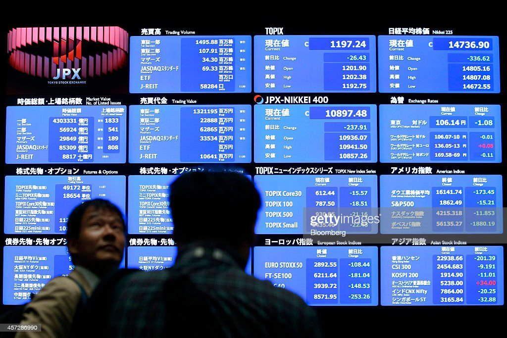 Visitors stand in front of an electronic stock board at the Tokyo Stock Exchange operated by Japan Exchange Group Inc in Tokyo Japan on Thursday Oct...
