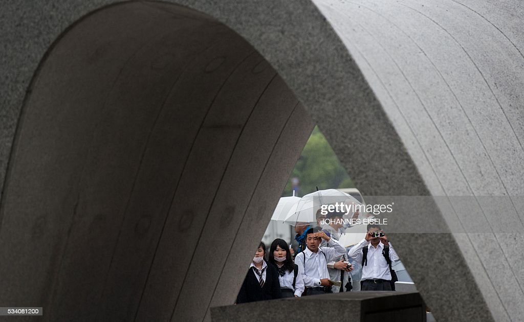 Visitors stand in front of the Hiroshima Peace Memorial park cenotaph in Naka Ward, Hiroshima Prefecture on May 25, 2016. Barack Obama is set to become the first sitting US president to visit Hiroshima when he journeys on May 27 with Japanese Prime Minister Shinzo Abe, hallowed ground to Japanese but, for more than 70 years, a no-go zone for 11 of his Oval Office predecessors. / AFP / JOHANNES
