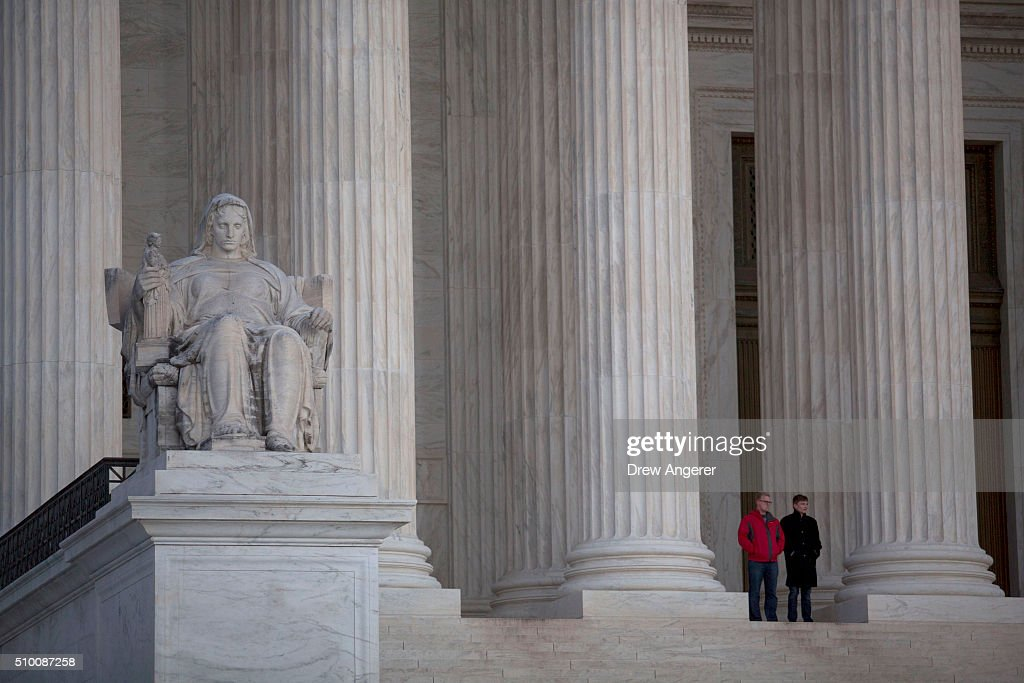 Visitors stand in front of the U.S. Supreme Court, February 13, 2016 in Washington, DC. Supreme Court Justice Antonin died on Saturday.