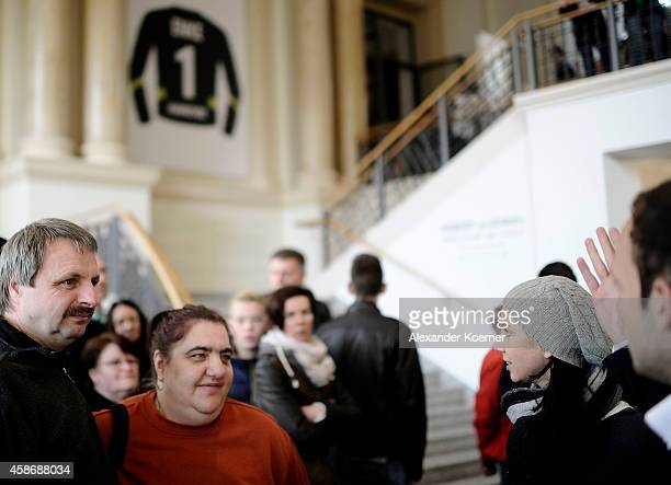 Visitors stand inside the special exhibition 'ROBERT gedENKEn' at State Museum and listen to a speach by Teresa Enke wife of Robert Enke on November...