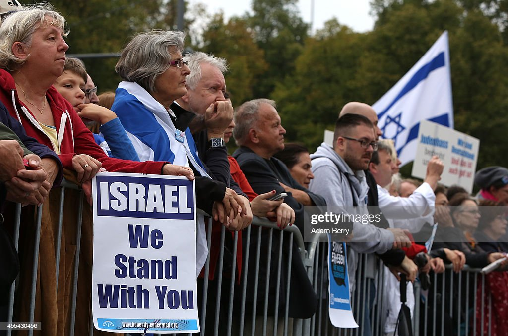 Visitors stand near a sign reading 'Israel We Stand With You' during a rally against antiSemitism on September 14 2014 in Berlin Germany With the...