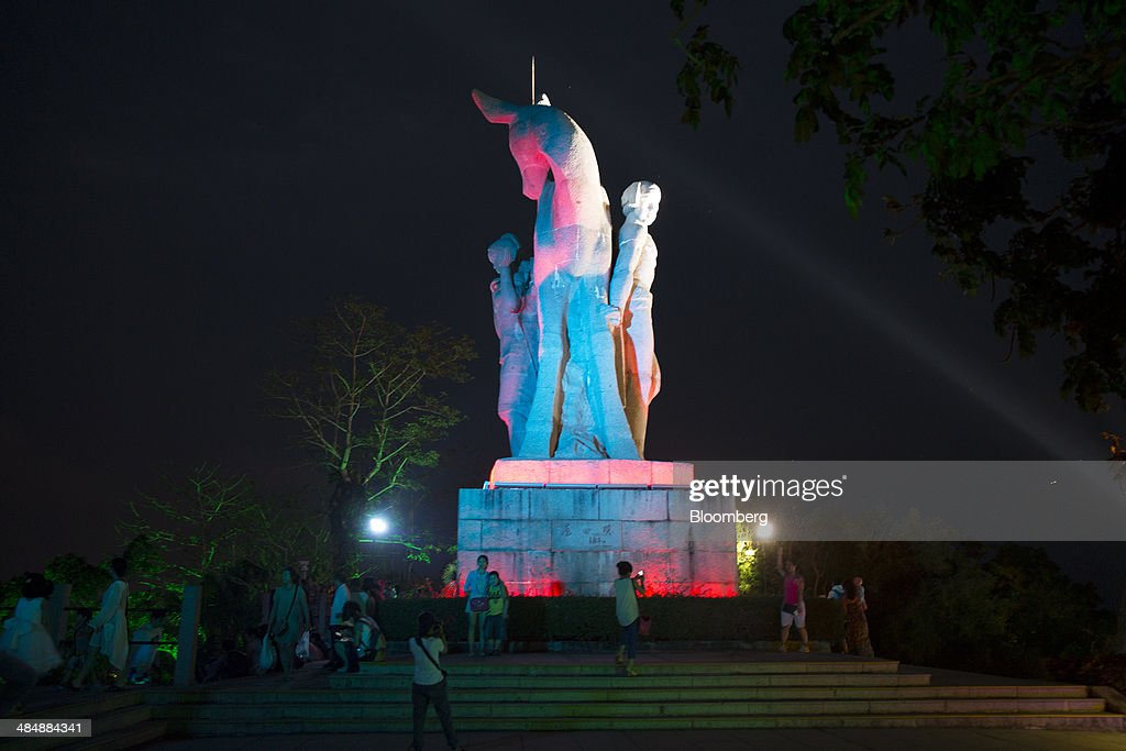 Visitors stand near an illuminated statue at Luhuitou Park in the Sanya Bay district of Sanya, Hainan, China, on Sunday, April 6, 2014. Chinas broadest measure of new credit fell 19 percent from a year earlier and money supply grew at the slowest pace since 2001, underscoring risks of a deeper slowdown as the government tries to curb financial dangers. Photographer: Brent Lewin/Bloomberg via Getty Images