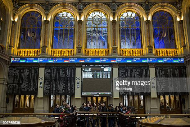 Visitors stand near electronic screens showing the performance of the Ibex 35 index at the Madrid stock exchange also known as Bolsas y Mercados...