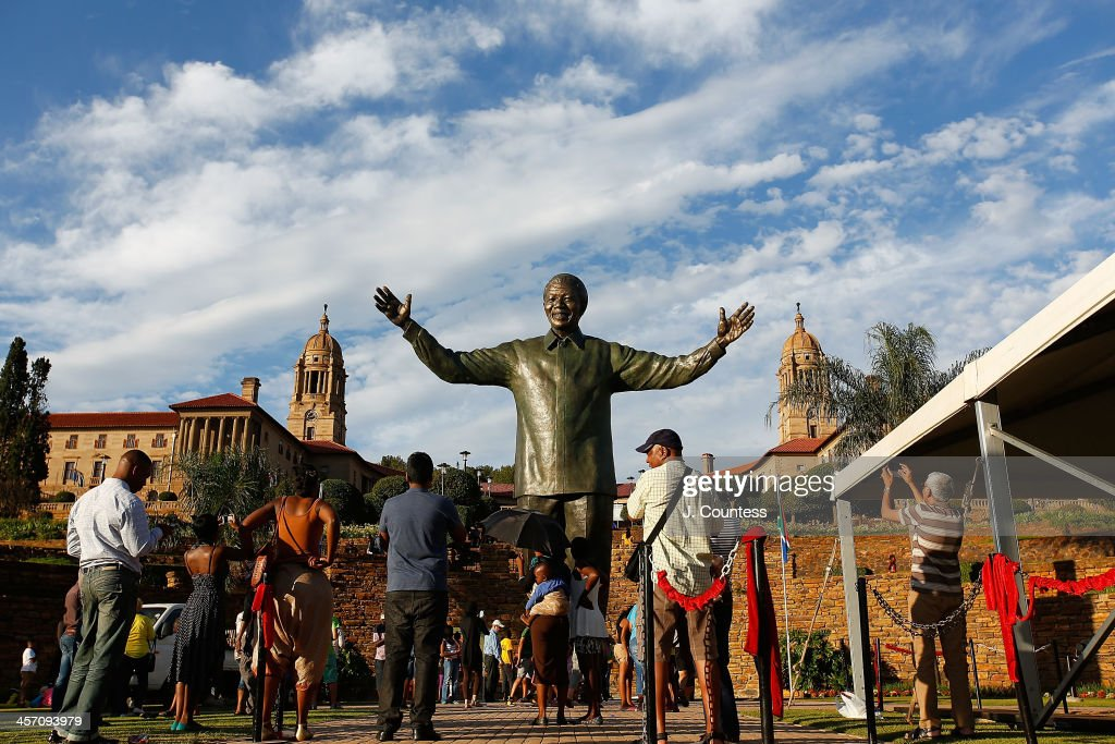 Visitors stand near the statue of Former South African President Nelson Mandela that was unveiled at the Union Buildings on December 16, 2013 in Pretoria, South Africa. The statue was dedicated on the day after the burial of Nelson Mandela in his home village of Qunu on December 15, 2013. Nelson Mandela passed away on the evening of December 5, 2013 at his home in Houghton at the age of 95. Mandela became South Africa's first black president in 1994 after spending 27 years in jail for his activism against apartheid in a racially-divided South Africa. December 16 is celebrated in South Africa as Reconciliation Day and marks several significant events in South African history.