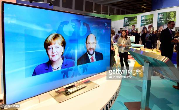 Visitors stand next to a television set showing the tvdebate between German Chancellor and leader of the conservative Christian Democratic Union...