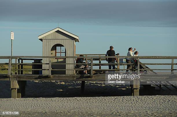 Visitors stand on a wooden walkway that crosses a wide beach on July 18 2016 at SanktPeterOrding Germany SanktPeterOrding is among the top...