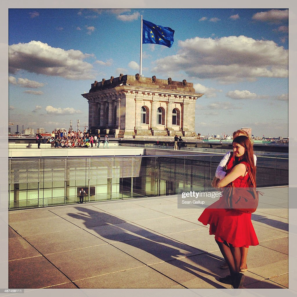 Visitors stand on the roof terrace as a flag of the European Union flies behind at the Reichstag on April 28, 2014 in Berlin, Germany. The Reichstag, home of the Bundestag, the German parliament, is among the city's major landmarks and a favourite tourist destination.