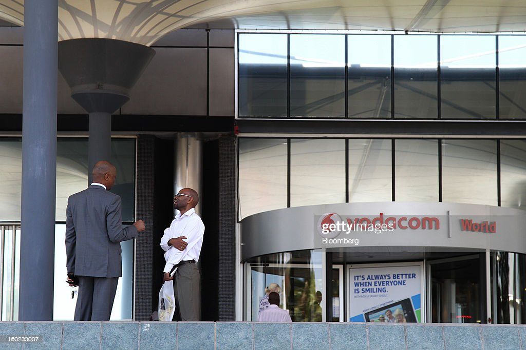 Visitors stand outside the entrance to the headquarters of Vodacom Group Ltd., Vodafone's biggest African business, in Johannesburg, South Africa, on Monday, January 28, 2013. Almost two decades after Vodafone Group Plc entered Africa, the region -- where most people earn less than $2 a day and mobile phone towers run on diesel -- is turning into one of the company's biggest profit generators. Photographer: Nadine Hutton/Bloomberg via Getty Images