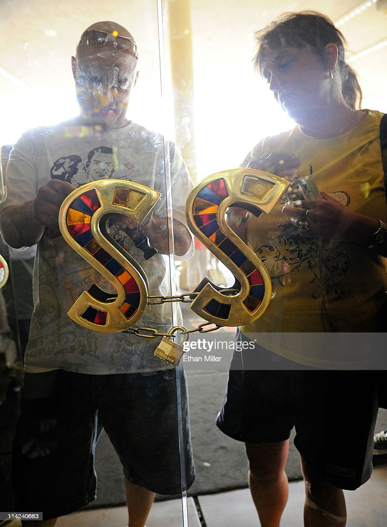 Visitors stand outside the Sahara Hotel & Casino behind locked door handles shortly before the property was closed on May 16, 2011 in Las Vegas, Nevada. The Sahara's current owner SBE Entertainment Group closed the 1,720-room resort, which first opened in 1952, and plans to redevelop the site in the future.