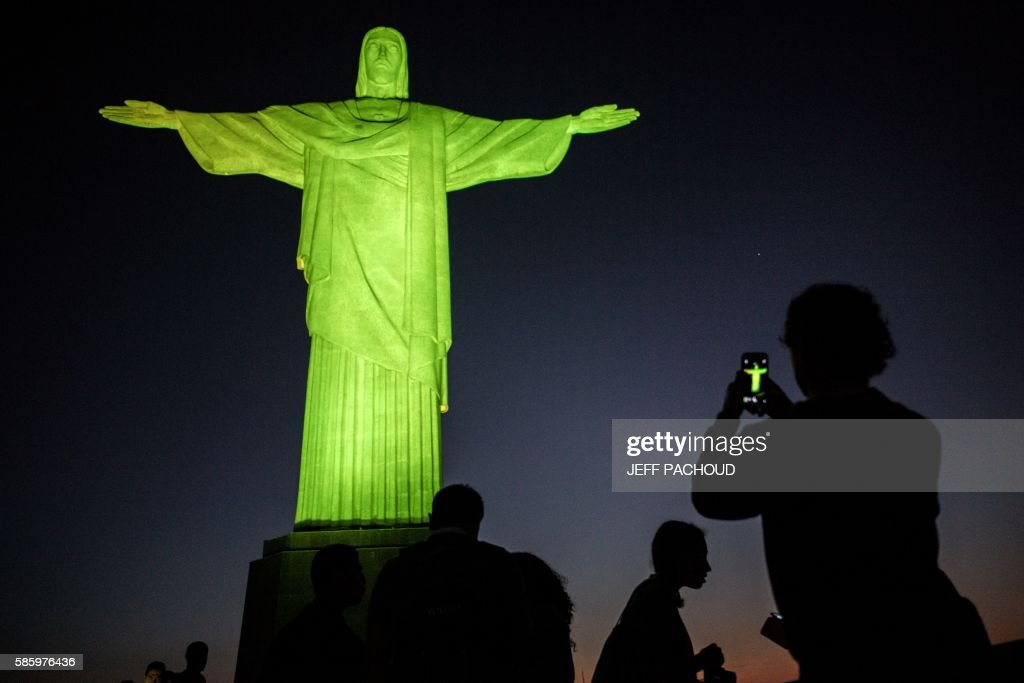 TOPSHOT - Visitors stand under the Christ the Redeemer statue on Corcovado mountain ahead of the Rio 2016 Olympic Games in Rio de Janeiro on August 4, 2016. / AFP / JEFF