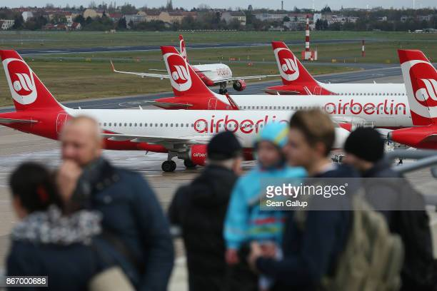 Visitors standing on a visitors' terrace look out at parked passenger planes of airliner Air Berlin at Tegel Airport on the last day of Air Berlin...