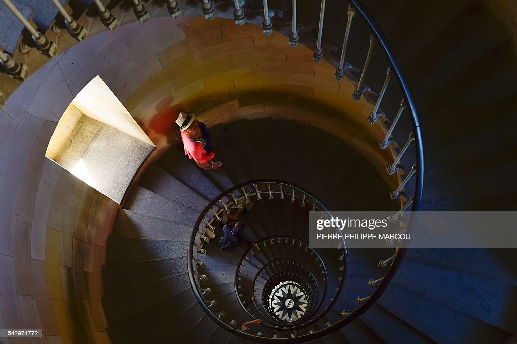 Visitors step down the staircase of the lighthouse of Saint Clement des Baleines on the Ile de Re island, western France, on June 25, 2016. / AFP / PIERRE