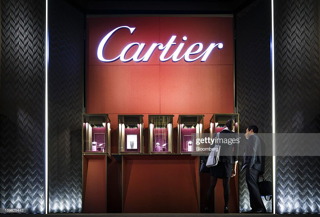 Visitors stop to inspect display cases at the Cartier, a unit of Cie. Financiere Richemont SA, booth during the first day of the Salon International de la Haute Horlogerie (SIHH) watch fair in Geneva, Switzerland, on Monday, Jan. 21, 2013. The Swiss watch industry slowed in the second half of 2012 as sales of timepieces and jewelry in Hong Kong, the biggest market for Swiss watchmakers, declined in August and October. Photographer: Valentin Flauraud/Bloomberg via Getty Images