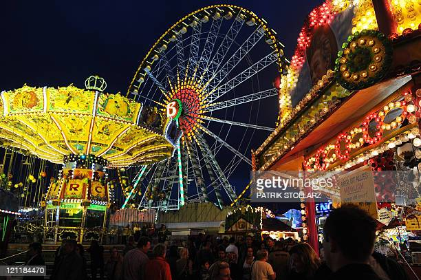 Visitors stroll across the annual funfair 'Cranger Kirmes' along the RhineHerne Canal in Herne western Germany on August 10 2011 The fair is one of...