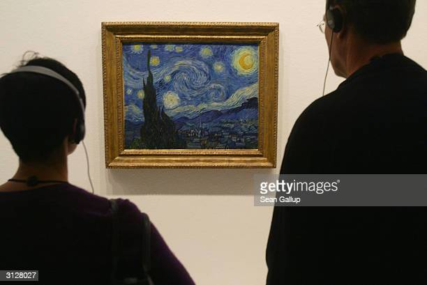 Visitors take a look at Vincent van Gogh's 'Starry Night' at the MoMA exhibit on March 24 2004 in Berlin Germany The exhibit which opened February 20...