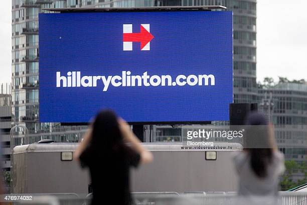 Visitors take a photograph of a Hillaryclintoncom billboard before the first 2016 Democratic candidate Hillary Clinton campaign rally at Four...