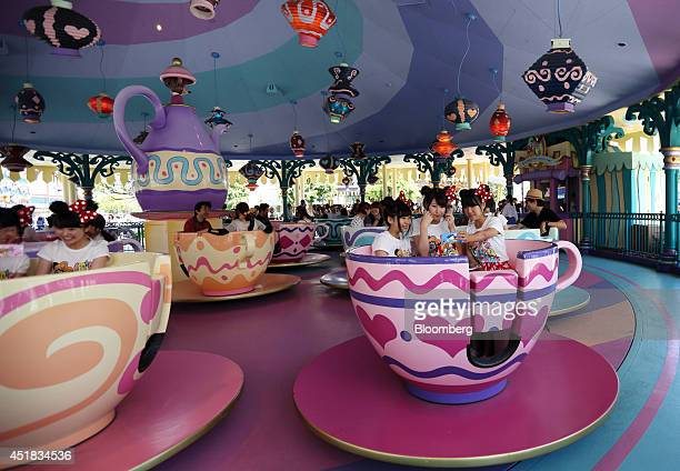 Visitors take a photograph using a smartphone as they ride on the Alice's Tea Party at Tokyo Disneyland operated by Oriental Land Co in Urayasu Chiba...