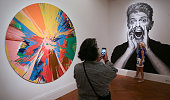 Visitors take a picture in front of a pictures of the British singer David Bowie and beside by one of the artworks he owned named 'BEAUTIFUL...
