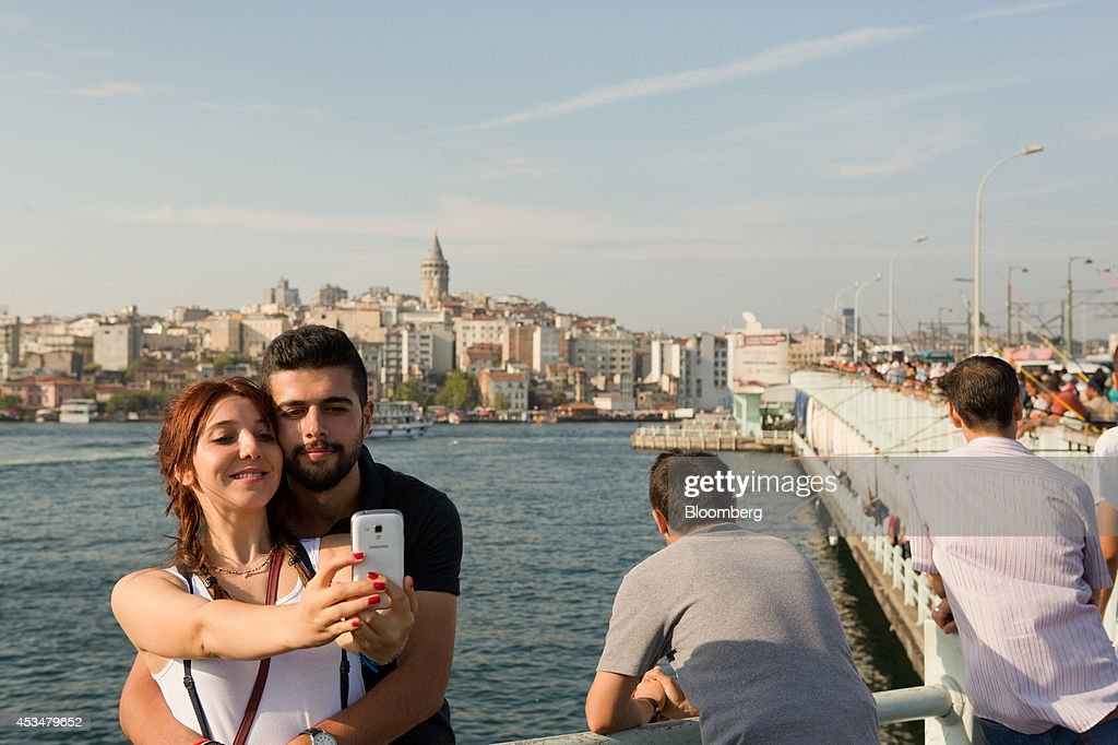 Visitors take a 'selfie' photograph on a smartphone against the backdrop of the Bosphorus strait in the Eminonu district of Istanbul, Turkey, on Sunday, Aug. 10, 2014. Investors said they will need to assess the next government's commitment to financial stability should Turkish Prime Minister Recep Tayyip Erdogan assume the presidency this month. Photographer: Kerem Uzel/Bloomberg via Getty Images