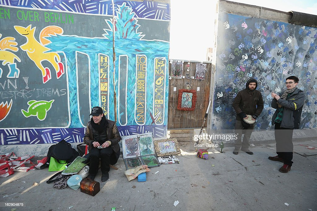 Visitors take it easy next to a section of the East Side Gallery, which is the longest still-standing portion of the former Berlin Wall, after attempts by construction workers to remove it with a crane were halted on March 1, 2013 in Berlin, Germany. Hundreds of protesters demonstrated and scuffled with police at the site earlier in the day after construction workers took out one narrow section. A real estate developer is planning to build a 14-storey apartment building between the Wall and the Spree River and needs to remove a 25-meter long Wall section in order to allow access to the construction site. Critics, including East Side Gallery mural artists and Spree River embankment development opponents, decry the move, citing the importance of the East Side Gallery's status as a protected landmark and a major tourist attraction. The East Side Gallery is approximately 1.3 kilometers long.