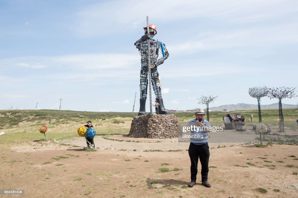 Visitors take photographs at a statue outside the Darkhan Metallurgical Plant in Darkhan, Mongolia, on Monday, Aug. 14, 2017. Mongolia, desperate to make more of its abundant resources as it seeks to revive its flailing economy, aims to make that vision a reality through one of the world's most ambitious power projects. The landlocked nation is considering a $7 billion plan to build coal, wind and solar plants that could send electricity across China, Russia, South Korea and Japan, according to the Shivee Energy Complex. Photograph: Taylor Weidman/Bloomberg via Getty Images