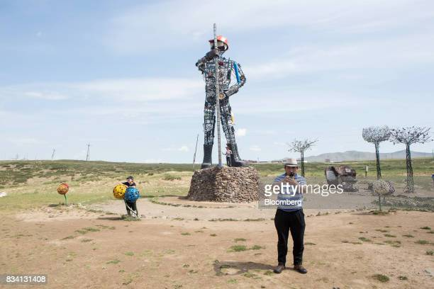 Visitors take photographs at a statue outside the Darkhan Metallurgical Plant in Darkhan Mongolia on Monday Aug 14 2017 Mongolia desperate to make...