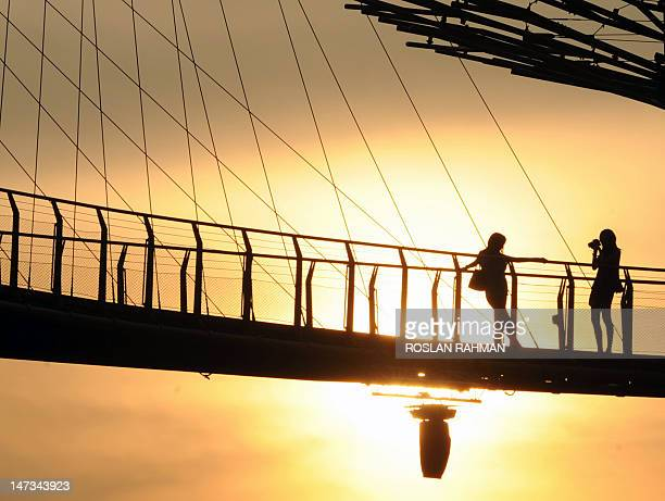 Visitors take photographs from the skyway walk linking across the towering Supertrees Grove in the Garden by the Bay in Singapore on June 28 2012...