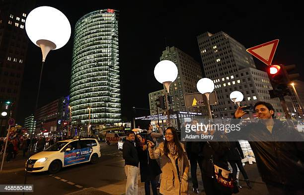 Visitors take photographs in front of a section of the light installation 'Lichtgrenze' or light border in front of Potsdamer Platz on November 7...