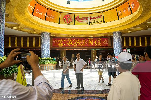 Visitors take photographs in front of the casino at Resorts World Sentosa operated by Genting Singapore Plc in Singapore on Thursday March 26 2015...