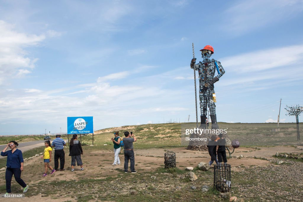 Visitors take photographs of a statue outside the Darkhan Metallurgical Plant in Darkhan, Mongolia, on Monday, Aug. 14, 2017. Mongolia, desperate to make more of its abundant resources as it seeks to revive its flailing economy, aims to make that vision a reality through one of the world's most ambitious power projects. The landlocked nation is considering a $7 billion plan to build coal, wind and solar plants that could send electricity across China, Russia, South Korea and Japan, according to the Shivee Energy Complex. Photograph: Taylor Weidman/Bloomberg via Getty Images