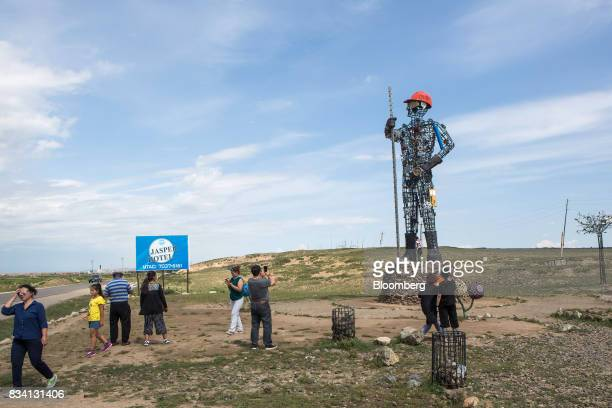Visitors take photographs of a statue outside the Darkhan Metallurgical Plant in Darkhan Mongolia on Monday Aug 14 2017 Mongolia desperate to make...