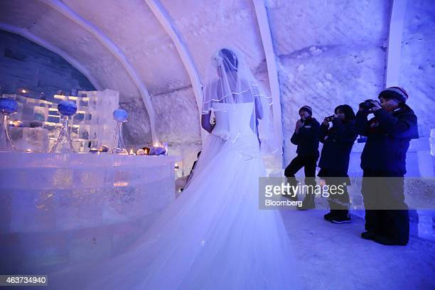 Visitors take photographs of a woman wearing a wedding dress during a ceremony to mark her tenth wedding anniversary inside the bar made from snow...