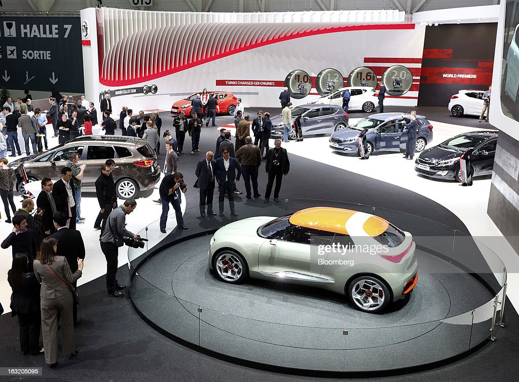 Visitors take photographs of the Kia Provo concept automobile, produced by Kia Motors Corp., on the second day of the 83rd Geneva International Motor Show in Geneva, Switzerland, on Wednesday, March 6, 2013. This year's show opens to the public on Mar. 7, and is set to feature more than 100 product premiers from the world's automobile manufacturers. Photographer: Chris Ratcliffe/Bloomberg via Getty Images